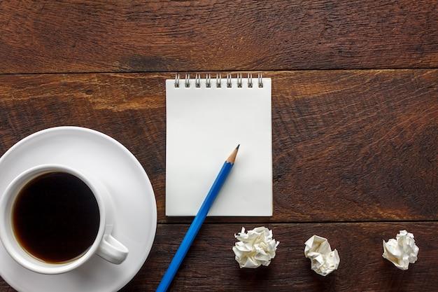 Ołówek widok z góry, papier notatkowy, zmięty papier czarny kawa na biurku biura z miejsca na kopię.