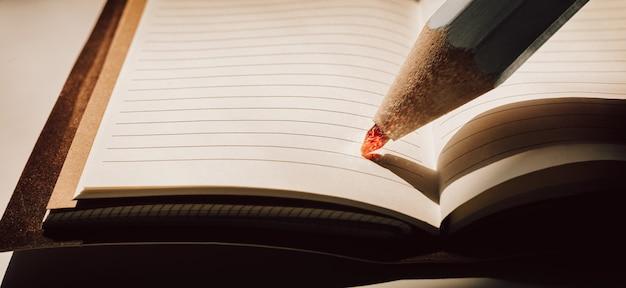 Ołówek z ognistym rysikiem znajduje się na kartce zeszytu. pojęcie biznesu, problemy społeczne, pożary lasów. różne środki przekazu