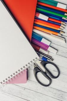 Ołówki do rysowania notatnik nożyczki biurowy drewniany stół