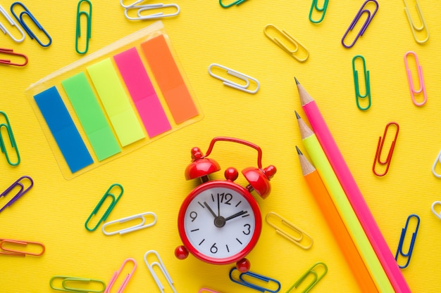 Ołówki i kolorowe spinacze do papieru, budzik