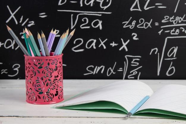 Ołówki i notatnik na tle tablica z wzorami matematycznymi