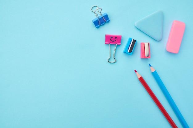 Ołówki, klipsy i gumka na niebieskim tle. artykuły biurowe, akcesoria szkolne lub edukacyjne, narzędzia do pisania i rysowania