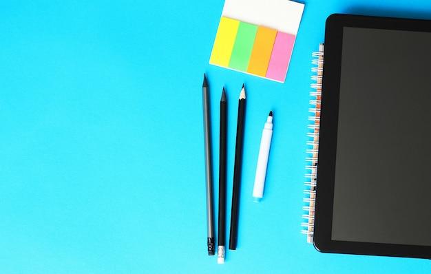 Ołówki, papier do pisania i tablett na niebieskim tle iz powrotem do koncepcji szkoły.