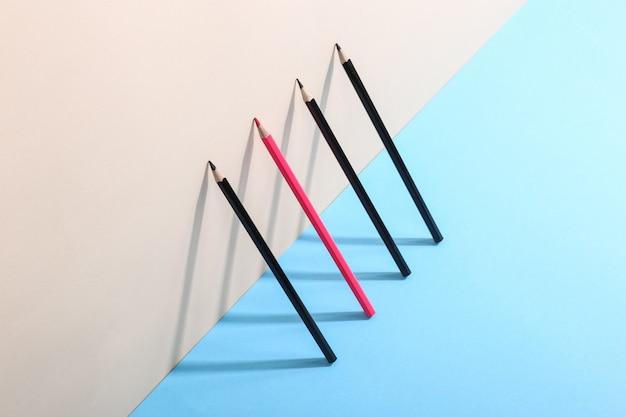 Ołówki stoją pod ścianą, rzucając cień, rysując geometryczne kształty.