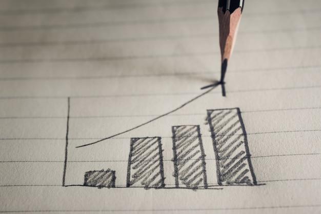 Ołówkowy rysunkowy biznesowy wykres na notatnika papieru biznesowym pojęciu.