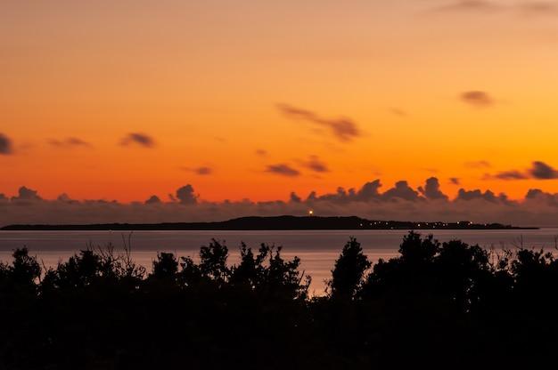 Olśniewające światło wschodu słońca w ciepłych kolorach, spokojne morze i sylwetka wyspy hatoma z oświetloną latarnią morską