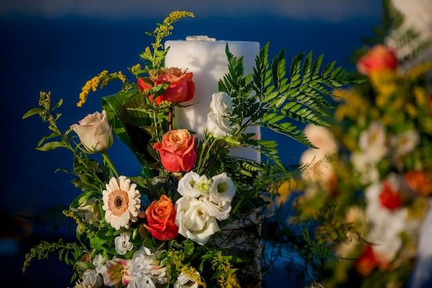 Ołtarz ślubny ozdobiony zielenią i pomarańczowymi kwiatami
