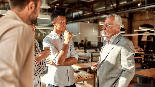 Omawiając nowy projekt trzech młodych kolegów rozmawia o czymś z pewnym siebie dojrzałym mężczyzną w