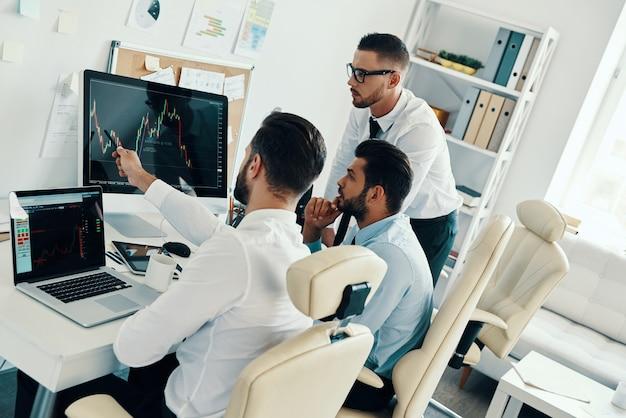 Omawiam szczegóły. grupa młodych, nowoczesnych mężczyzn w strojach formalnych, pracujących przy komputerach, siedząc w biurze