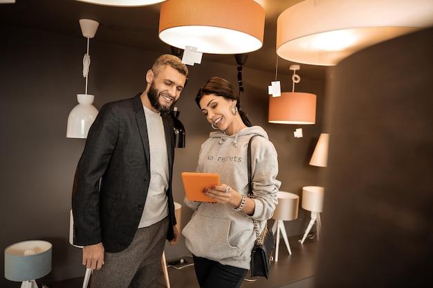 Omawianie informacji. uśmiechnięta dama w szarej bluzie z kapturem, prezentująca informacje na temat tabletu otoczonego lampkami