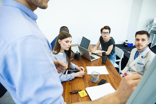 Omawianie postępów firmy. pewnie młody człowiek stojący w pobliżu tablicy i wskazując wykres, podczas gdy jego koledzy siedzą przy biurku.