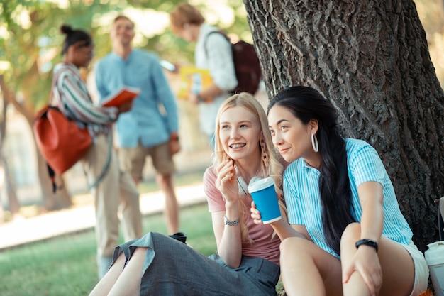 Omawianie pozorów. dwie uśmiechnięte dziewczyny siedzące pod wielkim drzewem pijące kawę i rozmawiające o swoich kolegach z grupy z przodu.