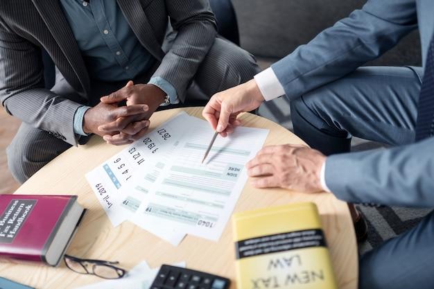 Omawianie szczegółów. zbliżenie wykwalifikowanego profesjonalnego prawnika podatkowego rozmawiającego z klientem i omawiającego szczegóły