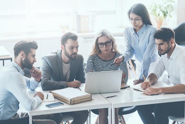 Omawianie zagadnień biznesowych. grupa młodych ludzi biznesu siedzących przy biurku i dyskutujących o czymś, patrząc razem na laptopa