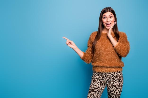 Omg czarny piątek! zdumiewająca funky dziewczyna wskazująca palcem wskazującym miejsce wskazuje niesamowitą promocję reklam polecam krzyk wow nosić dobry wygląd wiosna jesień strój izolowany niebieski kolor ściana