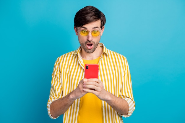 Omg kwarantanny przedłużone granice zamknięte. zdziwiony człowiek turysta korzysta ze smartfona pod wrażeniem sieci społecznościowej informacje reakcja nosić białe żółte ubrania na białym tle niebieski kolor tła