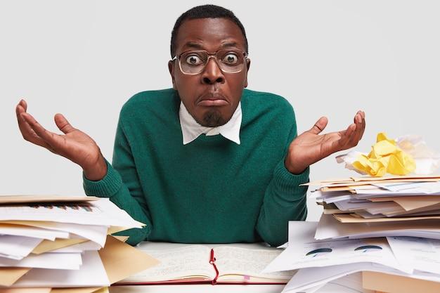 Omg, od czego zacząć? utalentowany pracownik biurowy ma nieświadomy oszołomiony wyraz twarzy, zaangażowany w proces pracy