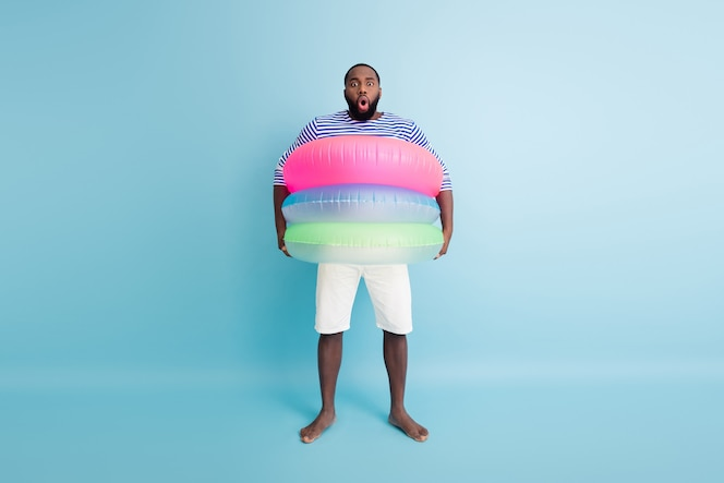 Omg, potrzebuję więcej ratowników! zdjęcie całego ciała zdziwiony szalony boso amerykański facet afroamerykanin spędza weekend turystyczny pod wrażeniem trzymaj pływak boje nosić kamizelkę białe spodenki izolowane niebieski kolor ściana