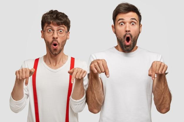 Omg, to imponujące. poziome ujęcie podekscytowanych, zdumionych dwóch młodych mężczyzn sapie ze zdumienia, wskazując palcami wskazującymi na podłogę, pobłogosławieni pomysłem, odizolowani na białej ścianie