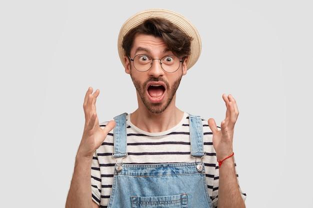 Omg, to straszne! wzruszający mężczyzna robotnik rolny gestykuluje ze złością, szeroko otwiera usta i wpatruje się w oczy, niezadowolony z sezonowych zbiorów, nosi swobodny wiejski strój