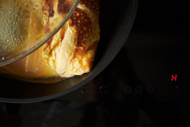 Omlet gotuje się na patelni, z bliska widok z góry