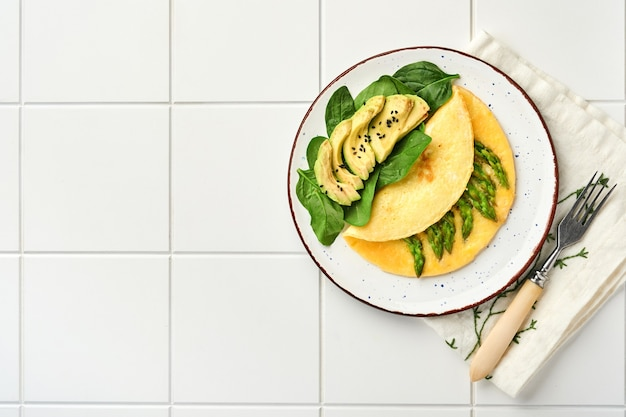 Omlet lub omlet nadziewany szparagami, awokado i liśćmi szpinaku na śniadanie na białym talerzu