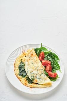 Omlet lub omlet ze szpinakiem, pomidorami cherry i przyprawami pieprzowymi na białym talerzu, na białym tle. widok z góry.