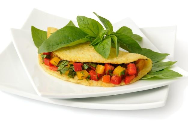 Omlet nadziewany warzywami z bazylią na białym tle