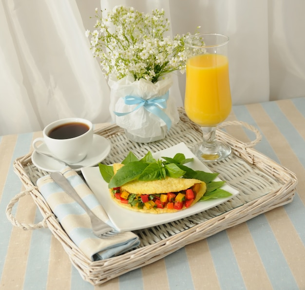 Omlet nadziewany warzywami z bazylią, sok pomarańczowy na tacy