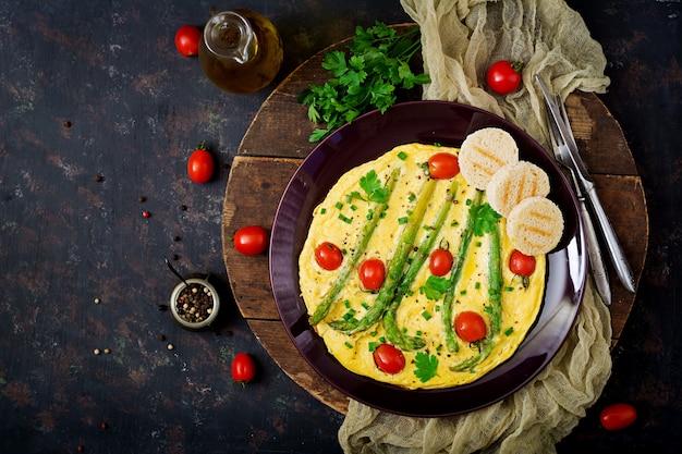 Omlet (omlet) z pomidorami, szparagami i zieloną cebulą