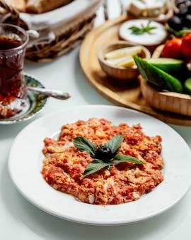 Omlet pomidorowy i czarna herbata w szklance armudu