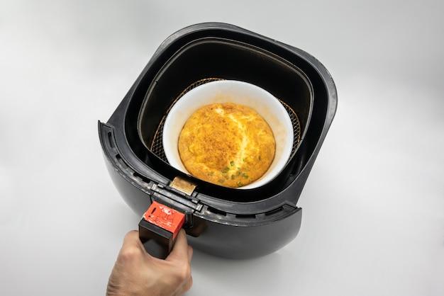 Omlet w białej ceramicznej misce w czarnym airfryer na białym tle.