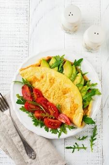 Omlet z awokado, pomidorami i rukolą na białym talerzu ceramicznym na jasnej kamiennej powierzchni. zdrowe śniadanie. selektywne skupienie. widok z góry. skopiuj miejsce.