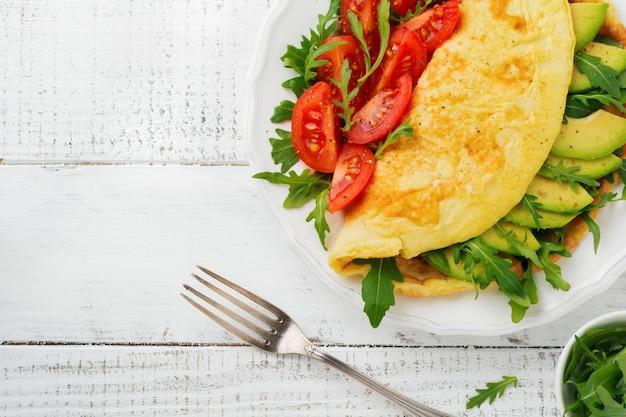 Omlet z awokado, pomidorami i rukolą na białym talerzu ceramicznym na jasnym kamiennym tle