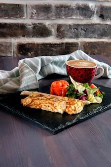 Omlet z łososiem na talerzu łupkowym i filiżance latte