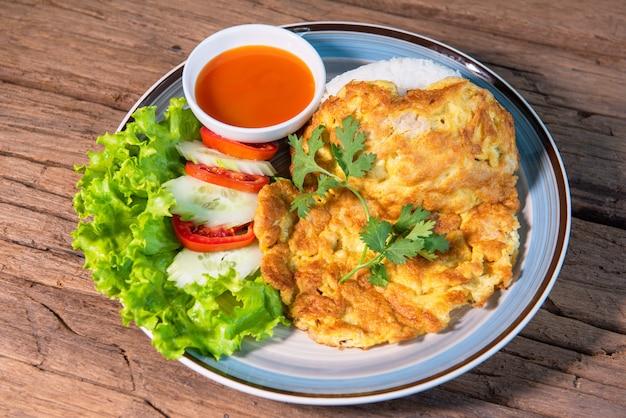 Omlet z mieloną wieprzowiną zwieńczony ryżem, podawany z sosem chili