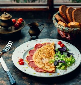 Omlet z pepperoni i zieloną sałatą.