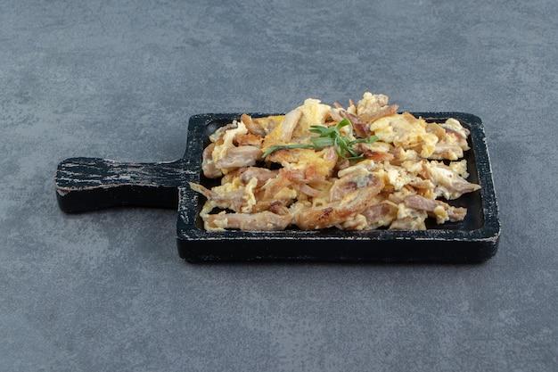Omlet z pokrojonym mięsem na czarnej tablicy.