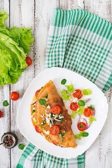 Omlet z pomidorami, natką pietruszki i serem feta na białym talerzu. widok z góry