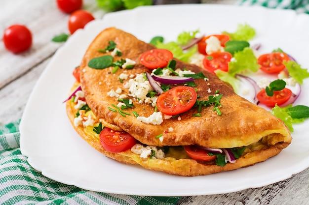 Omlet z pomidorami, natką pietruszki i serem feta na białym talerzu.