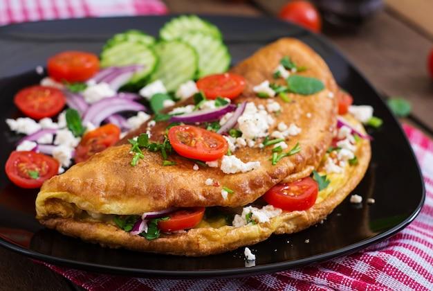 Omlet z pomidorami, natką pietruszki i serem feta na czarnym talerzu.