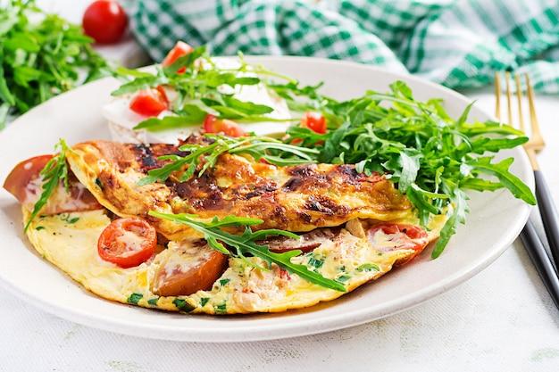 Omlet z pomidorami, serem i zielonymi ziołami na talerzu. frittata - włoski omlet.
