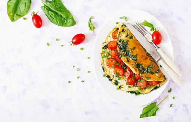 Omlet z pomidorami, szpinakiem i zieloną cebulą na białym talerzu. frittata - omlet włoski. widok z góry. leżał płasko.