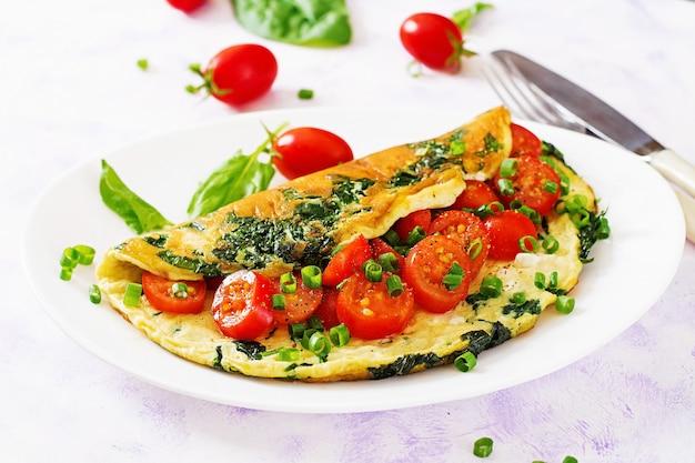 Omlet z pomidorami, szpinakiem i zieloną cebulą na białym talerzu.