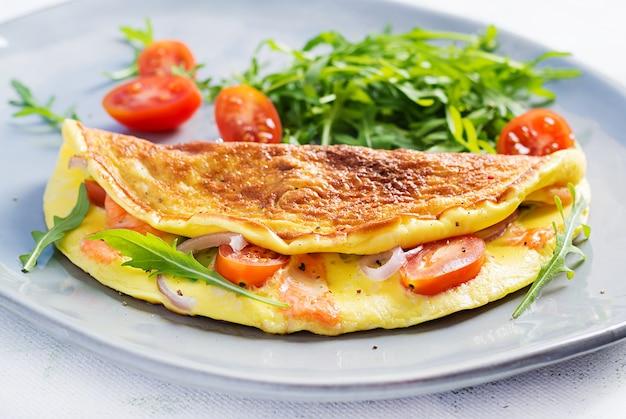 Omlet z serem, pomidorami i awokado na jasnym stole