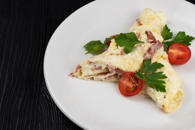 Omlet z szynką i serem na czarnym drewnianym tle