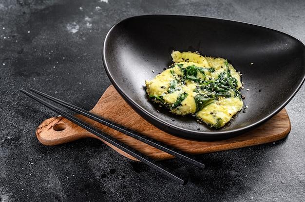 Omlet ze szpinakiem i serem z sezamem. czarne tło.