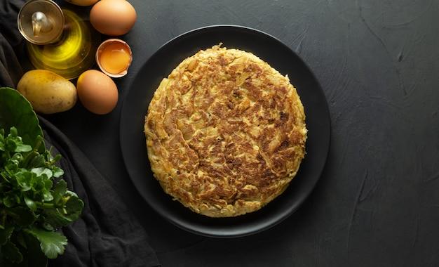 Omlet ziemniaczany na ciemnym tle drewniane