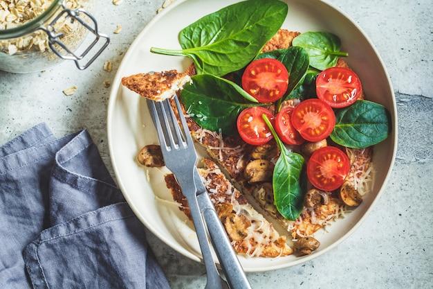 Omletowy placek owsiany z serem, pieczarkami, pomidorami i szpinakiem. zdrowe śniadanie fitness.