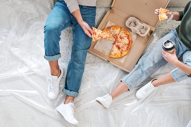 Omówienie młodej pary w stroju codziennym siedzącej na podłodze i jedzącej pizzę z pudełka i kawę po przeprowadzce do nowego mieszkania lub domu